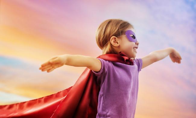 a little girl plays superhero