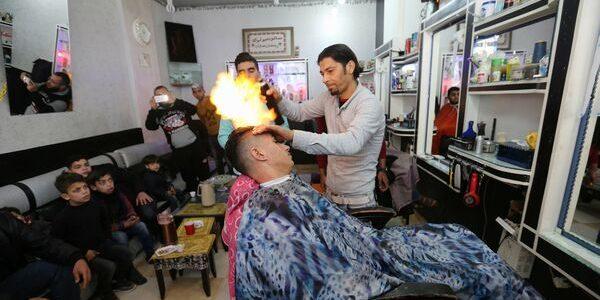 Un frizer oferă clienţilor servicii de îndreptare a părului cu…  flacăra